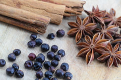 Spices on a wooden chopping board. A composition with some star anise, some juniper berries and three cinnamon sticks  on a wooden chopping board, landscape cut Stock Images