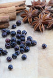 Spices on a wooden chopping board, slightly blurred. A composition with some juniper berries, some star anise and three cinnamon sticks on a wooden chopping Royalty Free Stock Photography