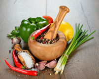 Spices, wooden mortar and vegetables Royalty Free Stock Image