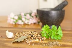 Spices on wooden table. Stone grinder and flowers  on the background Stock Image
