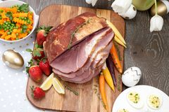 Spicey Ham For Easter. Delicious spicey roasted ham with deviled eggs, asparagus parmesan pastry, butternut squash with green peas, baby carrots, strawberries Royalty Free Stock Photos