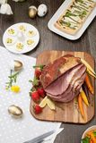 Spicey Ham For Easter. Delicious spicey roasted ham with deviled eggs, asparagus parmesan pastry, butternut squash with green peas, baby carrots, strawberries Royalty Free Stock Image