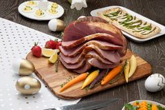 Spicey Ham For Easter. Delicious spicey roasted ham with deviled eggs, asparagus parmesan pastry, butternut squash with green peas, baby carrots, strawberries Stock Images