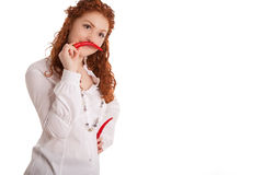 Spicy?. Funny and beautiful young caucasian girl with red haired demonstrating whiskers made of red chilly pepper and standing isolated on white background Royalty Free Stock Photos