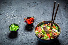 Spicy asian noodle in dark bowl with chopsticks Stock Images