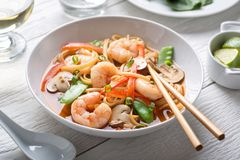 Spicy Asian Shrimp Noodle Soup. A bowl of delicious spicy asian shrimp noodle soup with mushroom, red pepper, snow peas and scallions royalty free stock image