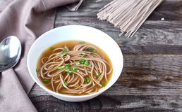 Spicy asian soup with soba noodles royalty free stock photo