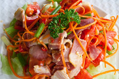Spicy bacon salad. With tomato carrot on white dish royalty free stock photography