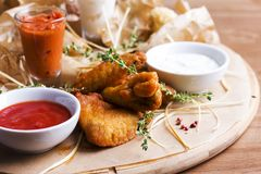 Spicy baked chicken wings with appetizers and sauces on round. Spicy baked chicken wings with appetizers and sauces on a round wooden Board Royalty Free Stock Photo