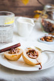Spicy baked pear with walnuts, honey, cinnamon sticks, healthy d Stock Images