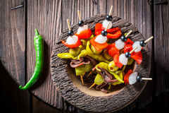 Spicy banderillas with peppers, olives and anchovies for spanish corrida. On wooden table Royalty Free Stock Photography