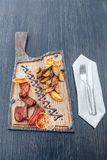 Spicy barbecue pork ribs served with french fries on a cutting board royalty free stock photo