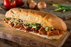 Spicy Barbecue Pork Submarine Sandwich. A delicious spicy barbecue pork submarine sandwich on a rustic wood table top Royalty Free Stock Images