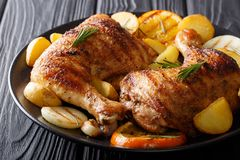 Spicy bbq chicken legs with grilled oranges, onions, garlic and. Potatoes close-up on a plate on a table. Horizontal royalty free stock photo
