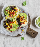 Spicy bean tacos with corn salsa and avocado  on a rustic cutting board on a dark background. Royalty Free Stock Photo