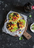 Spicy bean tortillas with corn salsa and avocado on a rustic cutting board on a dark background. royalty free stock image