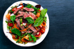 Spicy Beef Meat Salad with vegetables on blue stone. Royalty Free Stock Photo