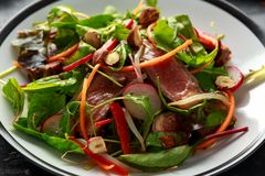Spicy Beef Salad with Carrots, radish, bean sprouts, chilli, nuts and green mix.  royalty free stock images