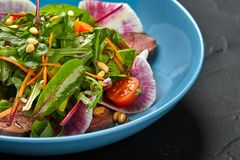 Spicy beef slices meat salad with tomatoes, parsley, radish and salad leaves spinach in a blue plate on a black table. Still life. Close-up Stock Photo