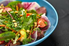 Spicy beef slices meat salad with tomatoes, parsley, radish and salad leaves spinach in a blue plate on a black table. Still life. Close-up Royalty Free Stock Images