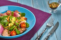 Spicy beef slices meat salad with tomatoes, parsley, radish and salad leaves spinach in a blue plate on a wooden table. Still life Stock Images