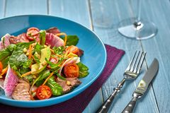 Spicy beef slices meat salad with tomatoes, parsley, radish and salad leaves spinach in a blue plate on a wooden table. Still life Stock Photo