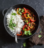 Spicy beef with vegetables and rice in a cast iron skillet on a dark background, top view. Asian style food Royalty Free Stock Photos