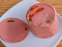 Spicy bologna slices in a white dish Royalty Free Stock Images