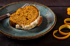 Spicy carrot-Orange cake. Spicy carrot and orange cake with frosting cream cheese, decorated with pecan nuts Stock Photos