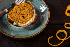 Spicy carrot-Orange cake. Spicy carrot and orange cake with frosting cream cheese, decorated with pecan nuts Royalty Free Stock Images