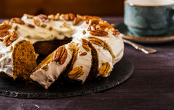 Spicy carrot-Orange cake. Spicy carrot and orange cake with frosting cream cheese, decorated with pecan nuts Stock Images