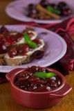 Spicy cherry jam. Homemade spicy cherry jam in a bowl and bread in the background stock photo