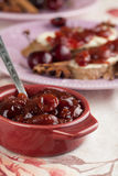 Spicy cherry jam. Homemade spicy cherry jam in a bowl and bread in the background royalty free stock photos