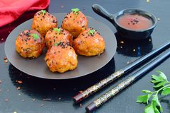 Spicy chicken balls in sweet chilli glaze on a metal tray. On a black wooden background Stock Photos