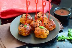 Spicy chicken balls in sweet chilli glaze on a metal tray. On a black wooden background Royalty Free Stock Images