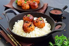 Spicy chicken balls in sweet chilli glaze with rice. In a frying pan on a black wooden background Royalty Free Stock Photos