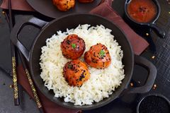 Spicy chicken balls in sweet chilli glaze with rice. In a frying pan on a black wooden background Royalty Free Stock Photo