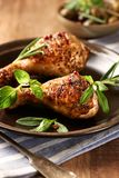 Spicy Chicken Legs with Herbs. Roasted chicken drumsticks, crispy golden brown skin. Vertical royalty free stock image