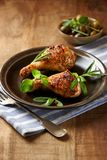 Spicy Chicken Legs with Herbs. Roasted chicken drumsticks on plate. royalty free stock photography