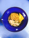 Spicy chicken noodle soup. Thai spicy needle soup with deep fried crispy Chinese dumpling in blue celadon Stock Photo