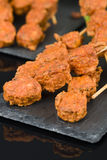 Spicy Chicken Satay. Marinated chicken meatball skewers served with chilli sauce and lemon wedges on a slate with reflections Stock Photos