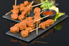 Spicy Chicken Satay. Marinated chicken meatball skewers served with chilli sauce and lemon wedges on a slate with reflections Stock Photography