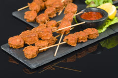 Spicy Chicken Satay. Marinated chicken meatball skewers served with chilli sauce and lemon wedges on a slate with reflections Royalty Free Stock Photo