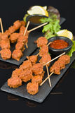 Spicy Chicken Satay. Marinated chicken meatball skewers served with chilli sauce and lemon wedges on a slate with reflections Royalty Free Stock Images