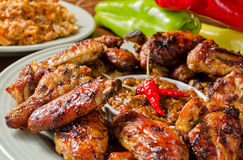 Spicy Chicken Wings. Spicy Jamaican style jerk chicken wings with rice and peppers Royalty Free Stock Images