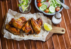 Spicy chicken wings and fresh vegetable salad. On wooden background Stock Photos