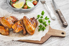 Spicy chicken wings and fresh vegetable salad Royalty Free Stock Image