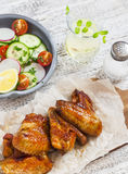 Spicy chicken wings and fresh vegetable salad Royalty Free Stock Images