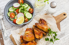 Spicy chicken wings and fresh vegetable salad. On wooden white background Stock Image