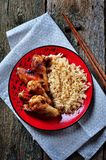 Spicy chicken wings with rice and herbs on an old wooden background Stock Photo